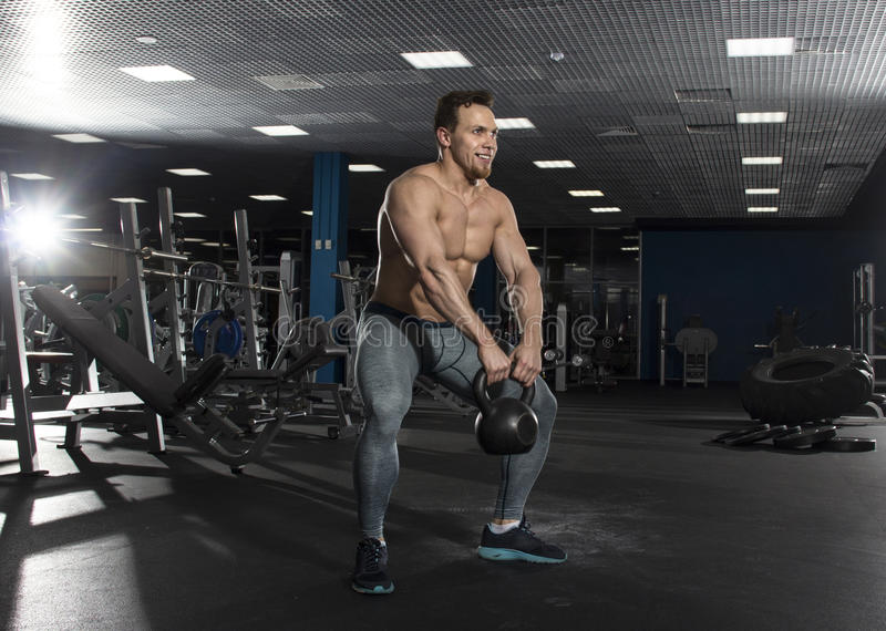 Muscular shirtless athlete doing kettlebell swings in modern fit stock photos