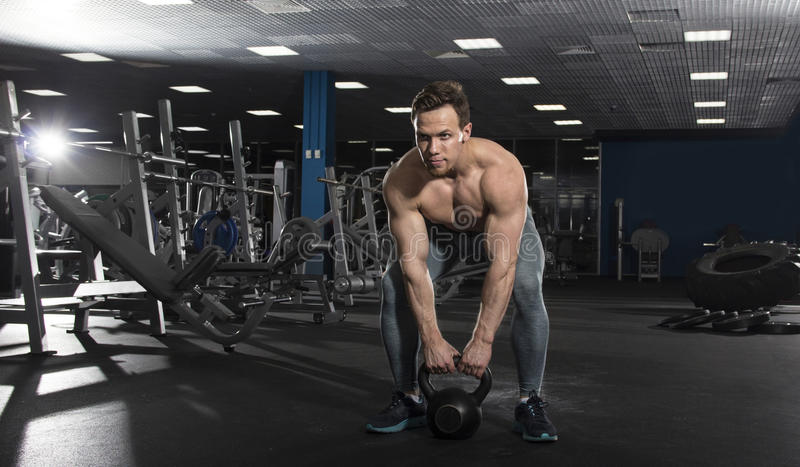 Muscular shirtless athlete doing kettlebell swings in modern fit stock images