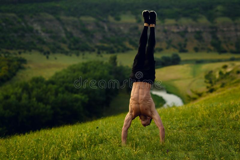 Attractive shirtless fit young man stand upside showing six pack abs on forest landscape background. Horizontal view. stock photo