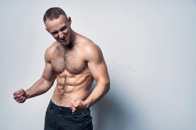 Muscular shirtless man celebrating success screaming stock images