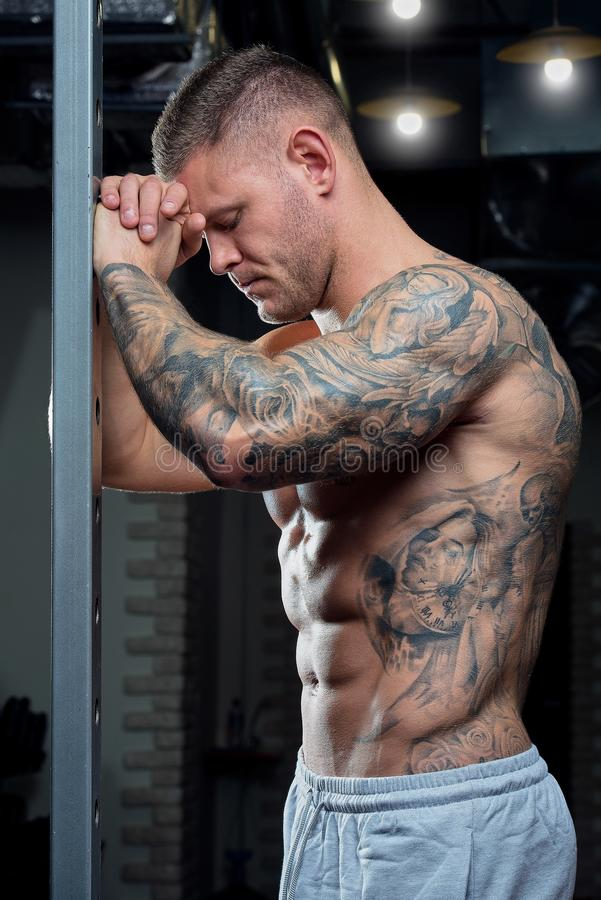 Muscular shirtless shredded strong tired man with blue eyes and tattoo poses on a power cage in a gray pants in a gym royalty free stock photography