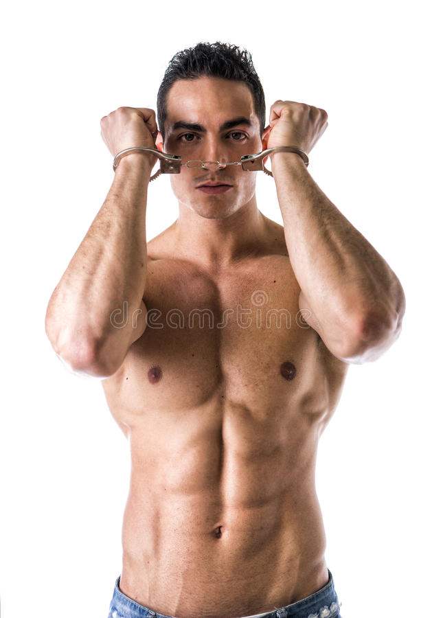 Muscular shirtless young man with handcuffs stock photo