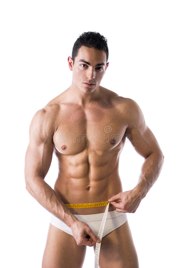 Muscular shirtless young man measuring waist with tape measure stock photo