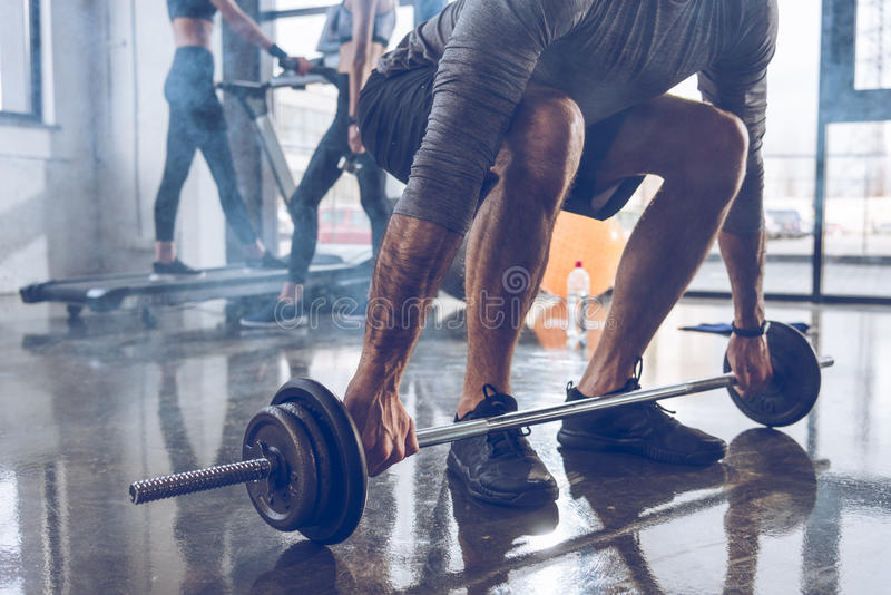 Muscular sportsman lifting barbell at gym workout royalty free stock photography