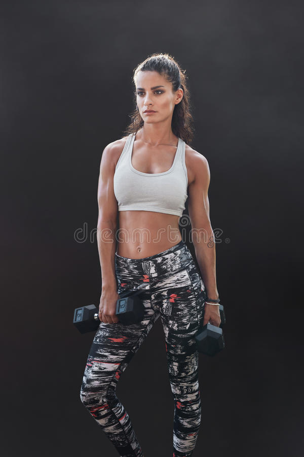 Muscular sportswoman with dumbbells. Vertical shot of muscular young woman in sportswear holding with weights and looking away. Female fitness woman with royalty free stock photography