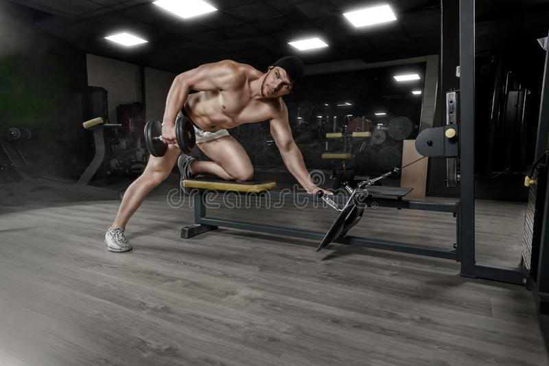 Muscular strong athletic bodybuilder doing one-arm dumbbell rows on bench in gym. Concept sport photo with copy space stock image