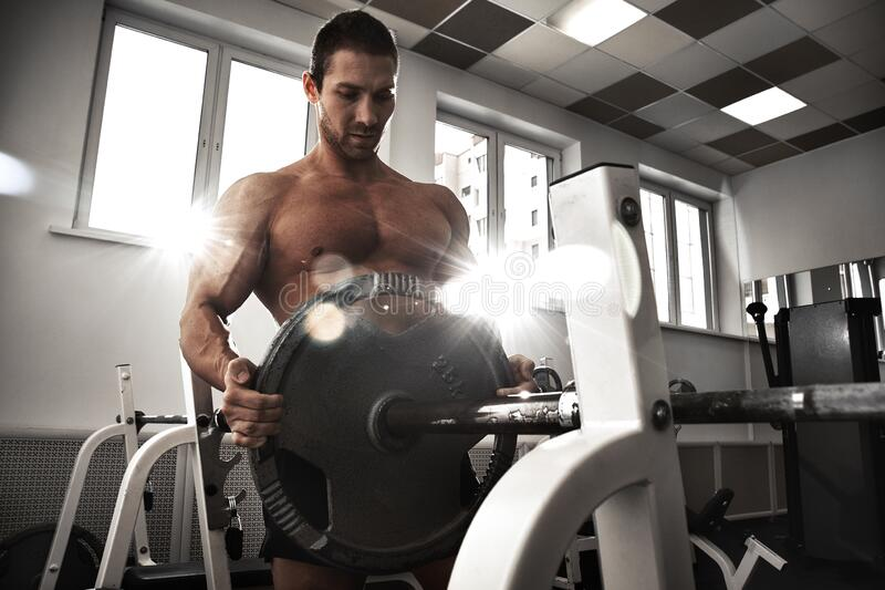 Strong Healthy Man Stretches Arms, Makes Weightlifting And