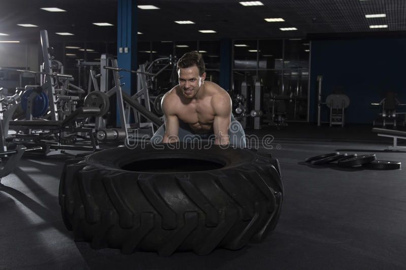 Muscular,Strong bodybuilder pushing tire in modern fitness cente royalty free stock images
