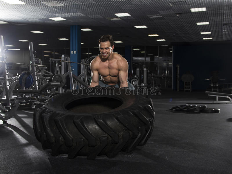 Muscular,Strong bodybuilder pushing tire in modern fitness cente stock images