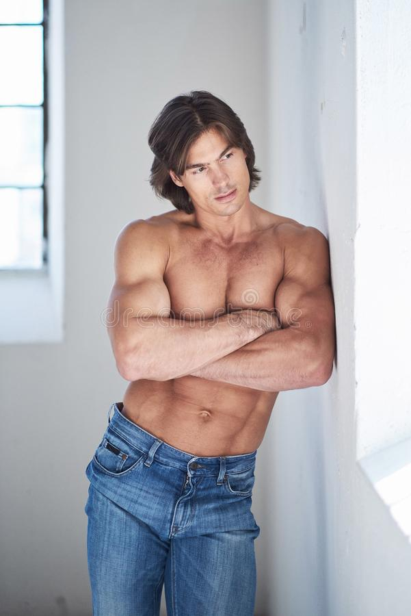 Muscular suntanned guy in denim jeans. Muscular suntanned guy in denim jeans with crossed arms posing in natural light stock images