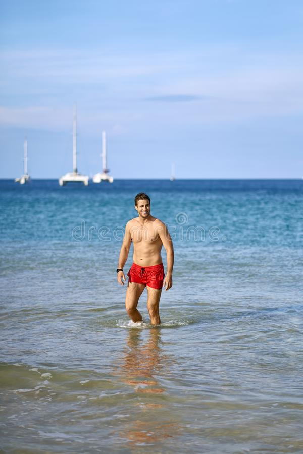 Tanned guy on beach. Muscular tanned man stands in the sea waves on the sunny background of the blue sky and white boats. He wears a red swim trunks and a dark royalty free stock image