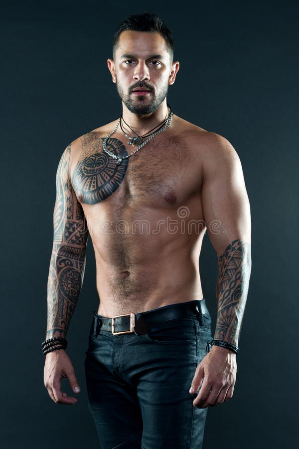 Muscular tattooed athlete look attractive. Sport and fashion concept. Handsome fit man posing wearing in jeans with. Tattoo. Tattoo art. Man handsome shirtless stock image