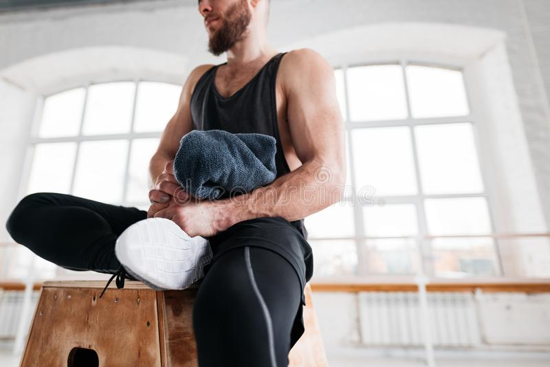 Perspiring fit athlete relaxing in sport gym after intense workout stock photo