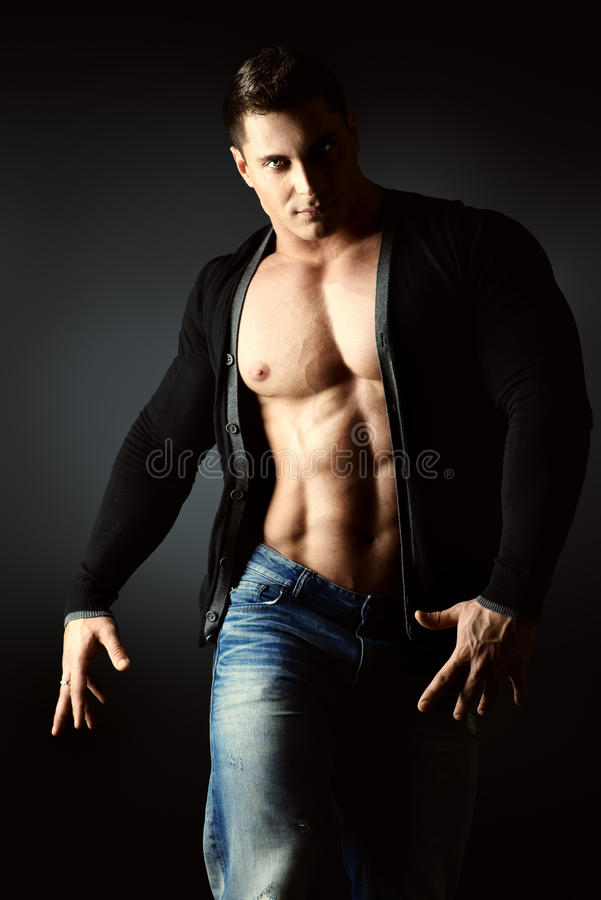 Muscular torso. Portrait of a muscular young man posing over dark background royalty free stock photos
