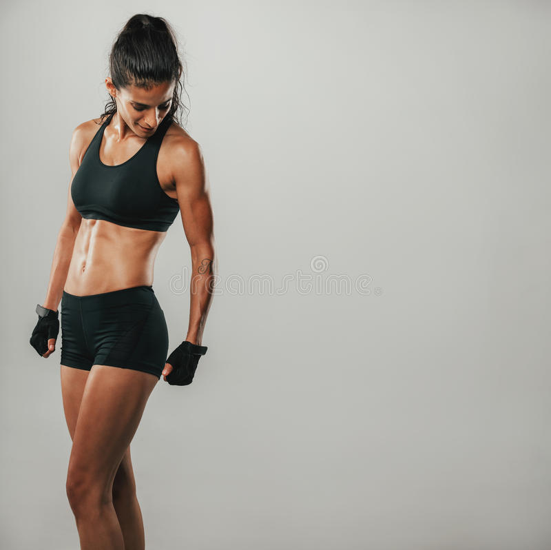 Muscular woman in black sports shorts and top. Looks down while standing in a grey room stock photos