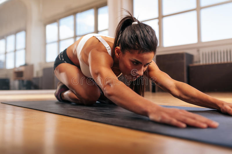 Muscular woman doing stretching workout in gym stock images