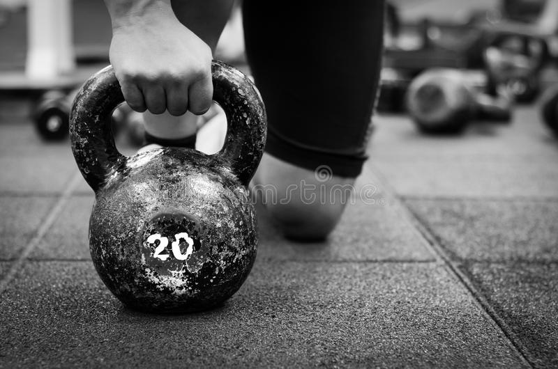 Muscular woman holding old and rusty kettle bell. On to the gym floor. Black and white kettlebell sport stock photos