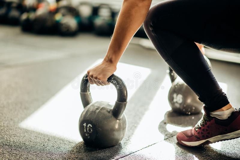 Muscular woman holding old and rusty kettle bell on to the gym floor royalty free stock image