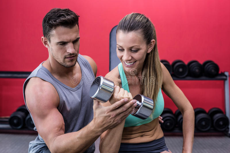 Muscular woman lifting a dumbbell. Trainer supervising a muscular women lifting a dumbbell stock photography