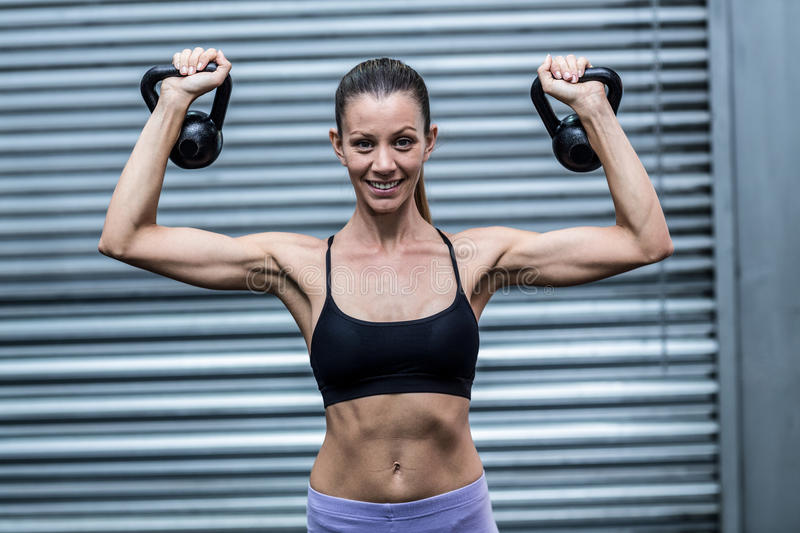 A muscular woman lifting kettlebells royalty free stock images
