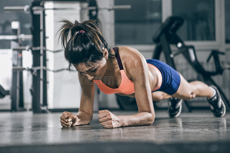 Muscular woman on a plank position. royalty free stock image