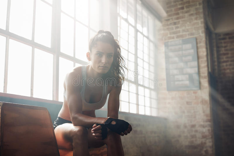 Muscular woman relaxing after workout at gym. Portrait of confident fitness trainer sitting on at gym. Muscular woman relaxing after workout royalty free stock photo