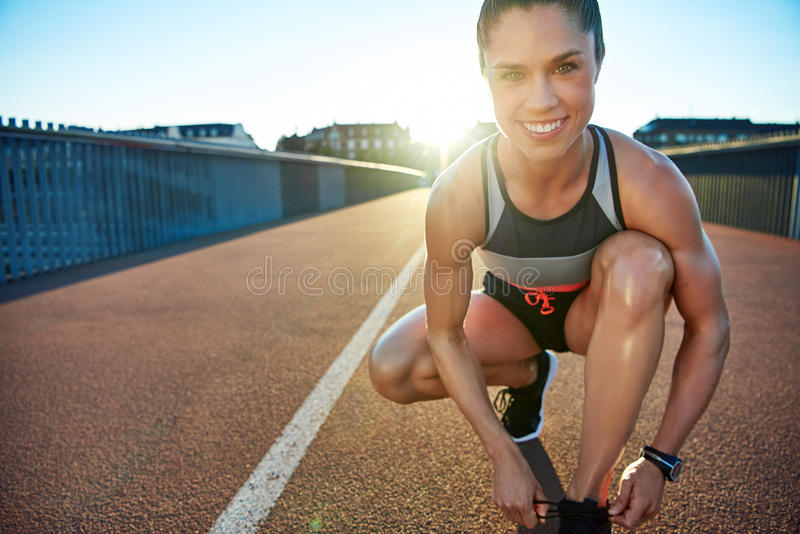 Muscular woman smiles at camera as she kneels stock images