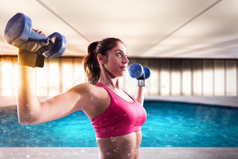Muscular woman is training with weights dumbbells stock image