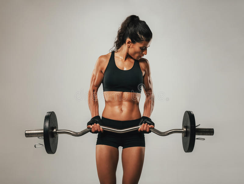 Muscular woman using barbell looking at her arms. Muscular young woman using curved barbell while looking at muscles bulging in her arms stock photography