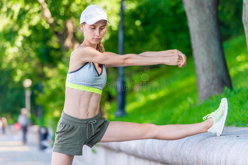 muscular woman warming up before jogging in a city park, portrait stock images