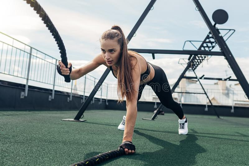 Muscular woman working out with battle ropes royalty free stock images