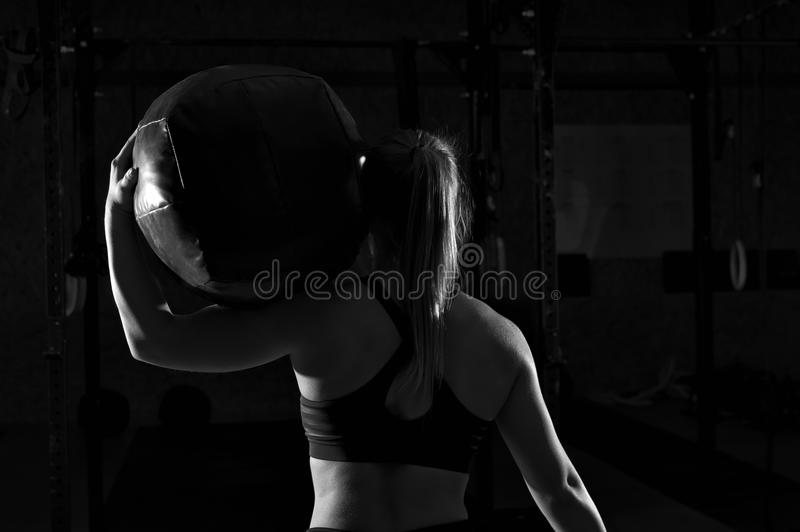 Muscular woman working out in gym with heavy ball royalty free stock photography