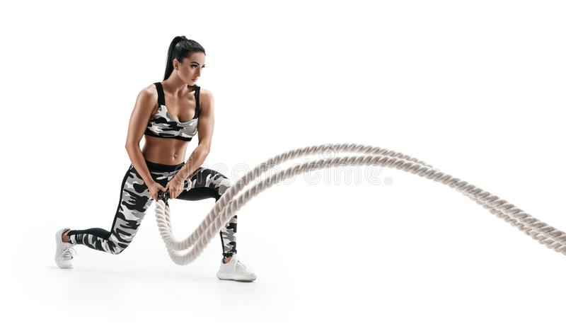 Muscular woman working out with heavy ropes. stock image