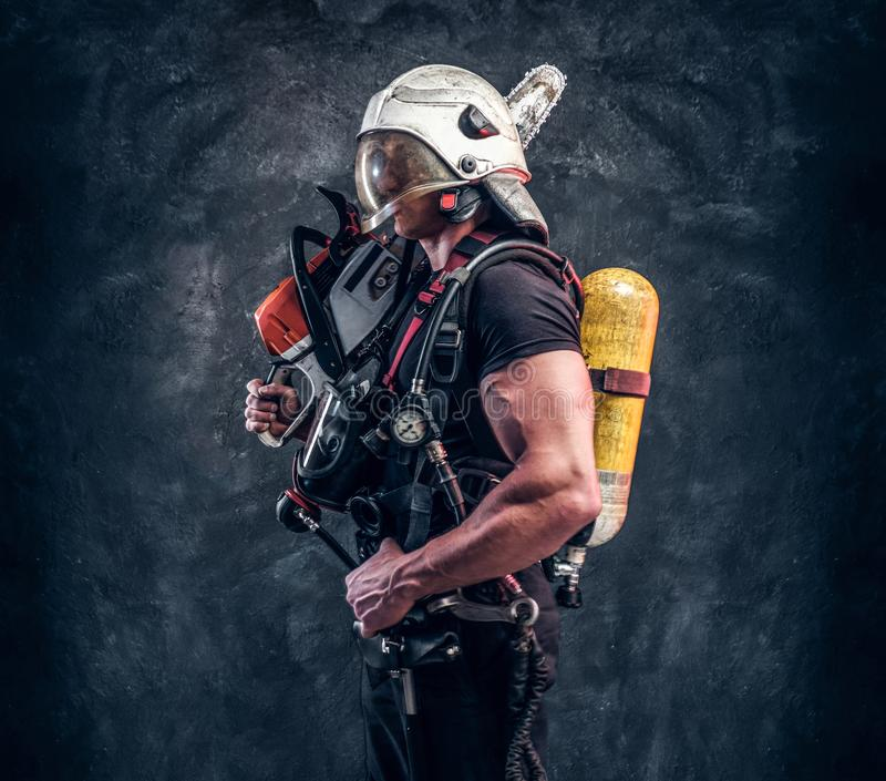 Portrait of muscular man with chainsaw and respirator stock images