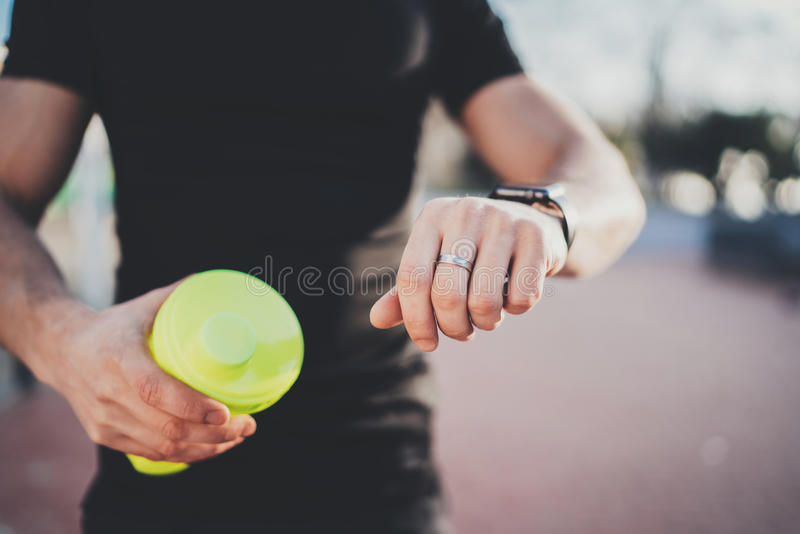 Muscular young athlete checking heart rate and calories on his smartphone application after good workout outdoor session royalty free stock image