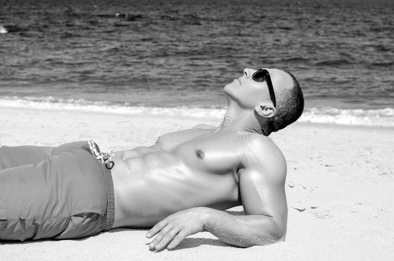 Muscular young athletic man lying on the beach stock photo