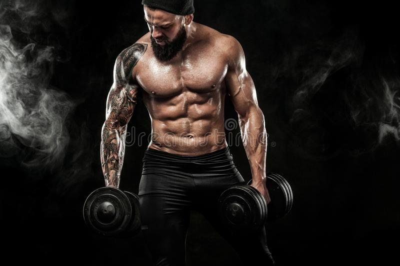Muscular young fitness sports man workout with dumbbell in fitness gym stock photos
