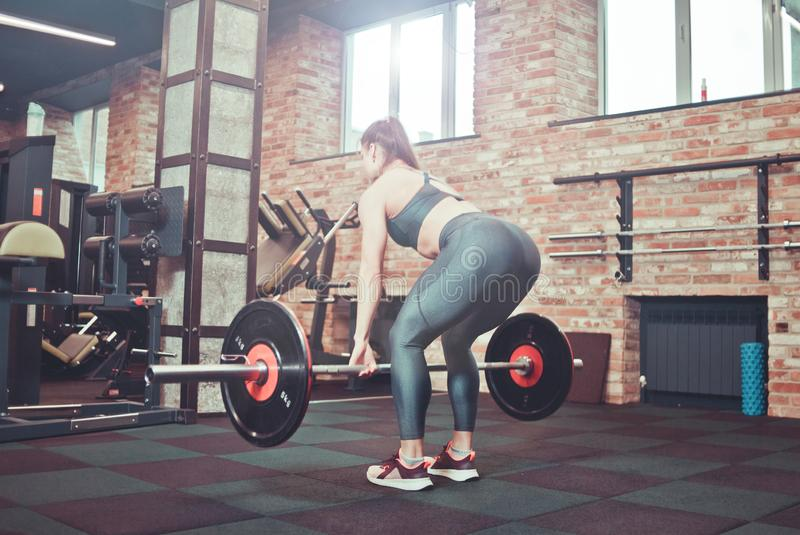 Muscular young fitness woman doing heavy deadlift royalty free stock photography