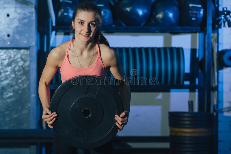 Muscular young fitness woman lifting a weight crossfit in the gym. Crossfit woman. Crossfit style. Crossfit and fitness royalty free stock photos