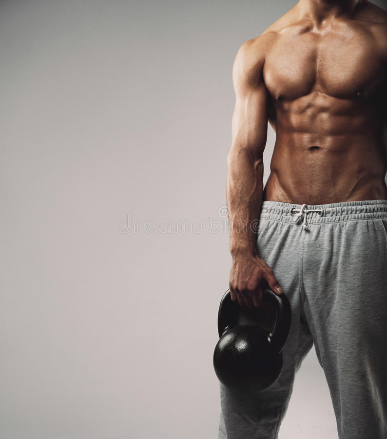 Muscular young guy with kettle bell. Cropped image of young man in sweatpants holding kettle bell. Crossfit workout theme on grey background work with empty copy royalty free stock photos