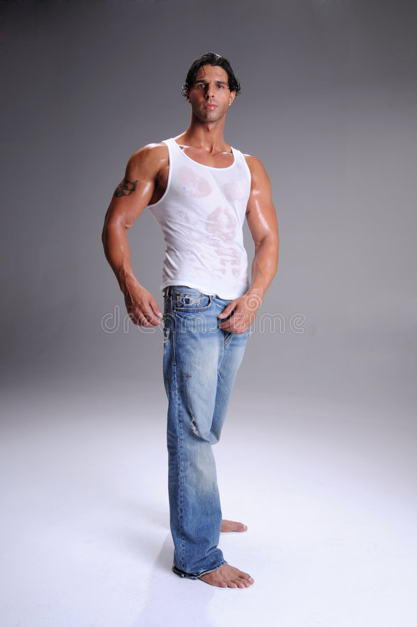 Muscular Young Man. Standing in jeans and a white wife beater tee shirt royalty free stock images