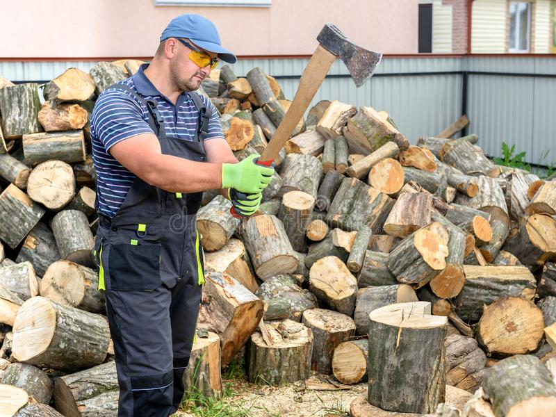 Muscular young man chopping logs stock photography