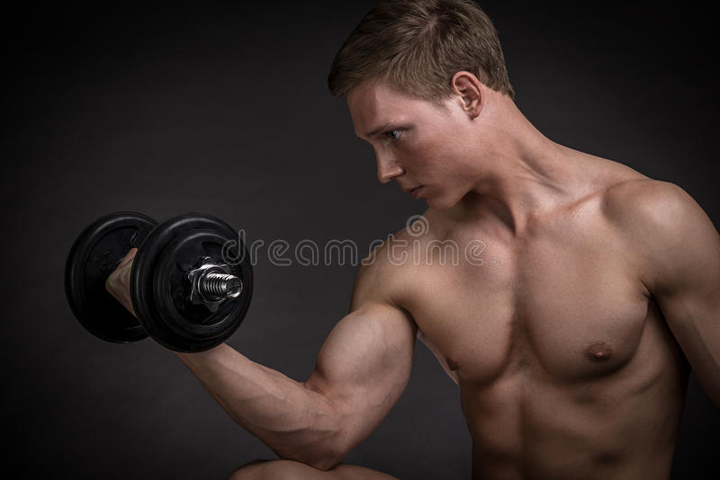 Muscular young man doing exercise with dumbbells stock photos