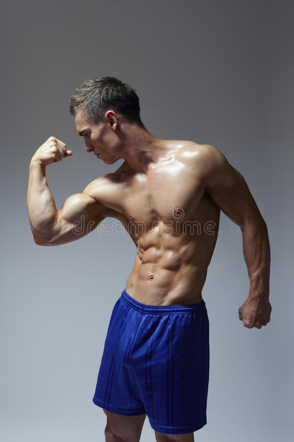 Muscular Young Man Flexing Arm Muscles Stock Photo