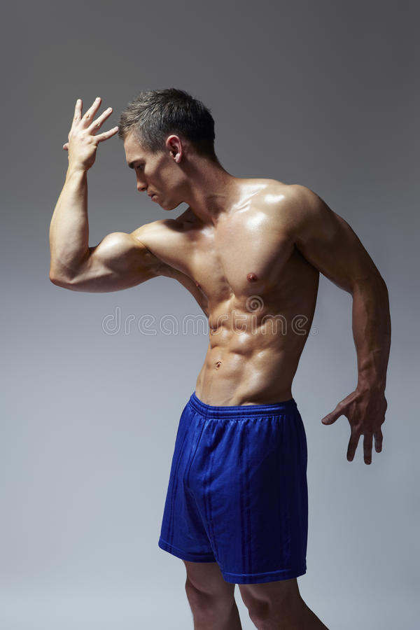 Download Muscular Young Man Flexing Arm Muscles In Sports Outfit Royalty Free Stock Photo - Image: 28548265