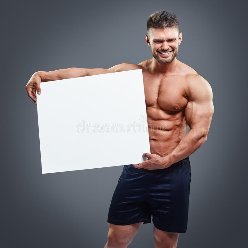 Muscular young man holding blank white poster. Healthy muscular young man holding blank white poster and smiling isolated on gray background. Handsome athlete royalty free stock photos