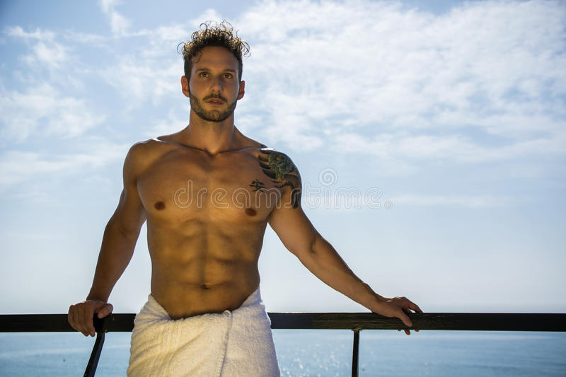 Muscular young man leaning on hand-railing on cruise ship stock photos