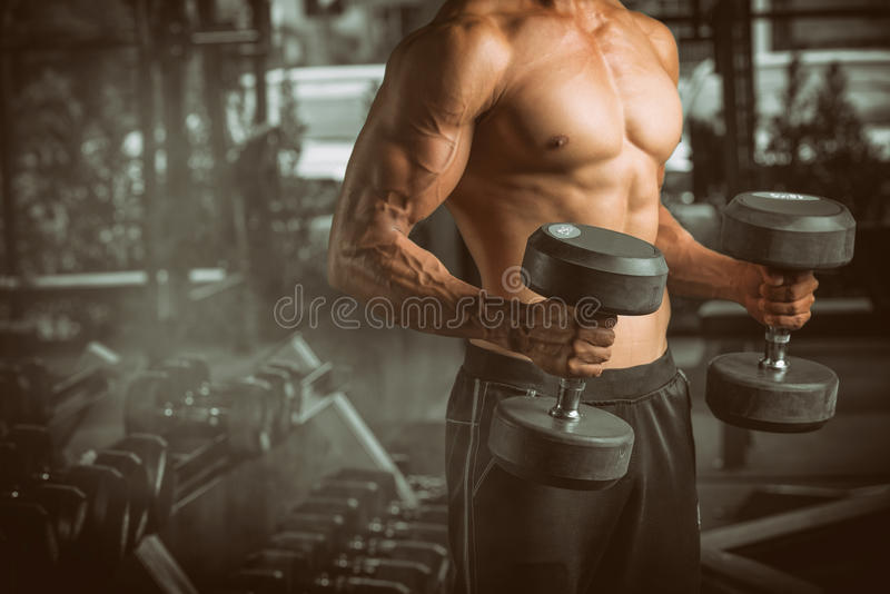 Muscular young man lifting weights at fitness center. royalty free stock photos