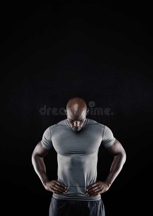 Muscular young man looking down stock photo