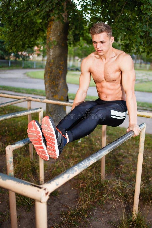 Muscular young man pull ups the horizontal bar. Street workout stock image